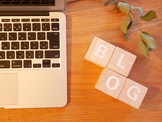ノートパソコンと「BLOG」と書かれたブロック