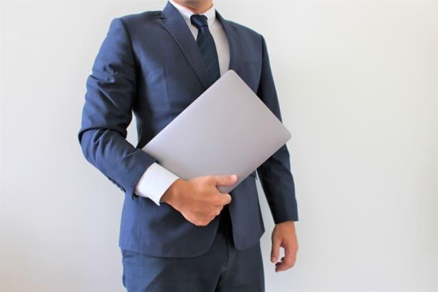 ノートパソコンを手にする男性