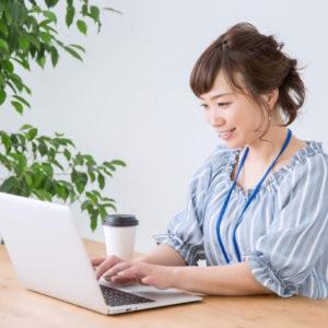 パソコンを使用している青い服の女性